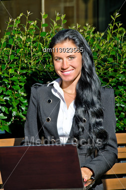 Attractive Businesswoman With Notebook Sitting In City Park Stock Photo
