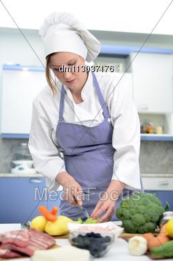 Attractive Chief Cook Preparing Food, Cuts Broccoli Stock Photo