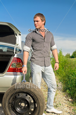 Attractive Male Changing Tires On The Road Stock Photo