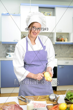 Attractive Smiling Chief Cook Preparing Food, Peeling Potatoes Stock Photo
