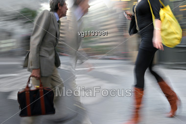 Attractive Woman Walking On A City Street Holding Mobile Phone In Motion Blur, Walking By Businessman Staring On Her Stock Photo