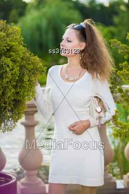 Attractive Woman Wearing White Dress Posing Outside Stock Photo