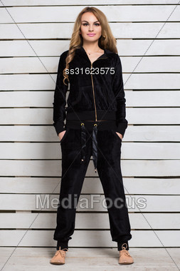 Attractive Young Blond Woman In Black Clothes Posing Near White Wooden Wall Stock Photo