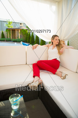 Attractive Young Blond Woman Relaxing In Summer House Stock Photo