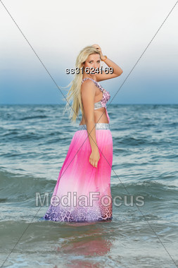 Attractive Young Blonde In Pink Dress Posing In The Water Stock Photo