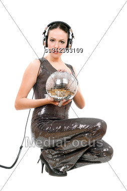 Attractive Young Brunette In Headphones With A Mirror Ball. Stock Photo