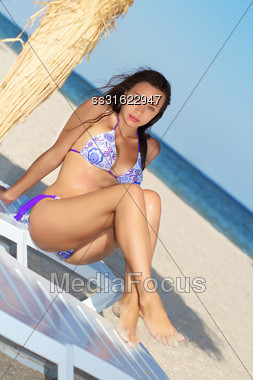 Attractive Young Brunette Posing On The Beach Bed Stock Photo