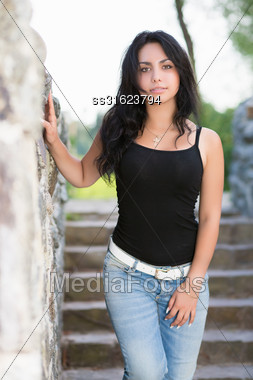 Attractive Young Brunette Posing Near The Stone Wall Stock Photo