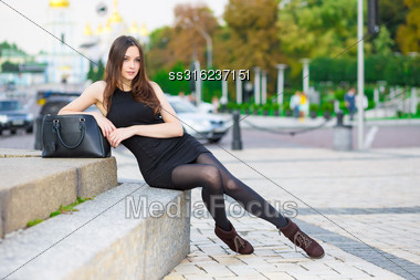 Attractive Young Brunette Wearing Black Dress Posing Near The Road Stock Photo