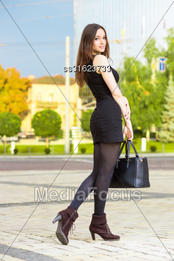 Attractive Young Brunette Wearing Black Dress Posing With Handbag Stock Photo