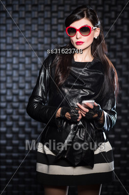 Attractive Young Brunette Wearing Black Jacket And Red Sunglasses Posing With A Mobile Phone Stock Photo