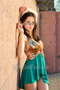 Attractive Young Lady In Golden And Turquoise Dress Posing Near The Wall Outdoors Stock Photo