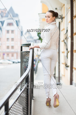 Attractive Young Lady In White Pants And Jacket Posing Outdoors Stock Photo