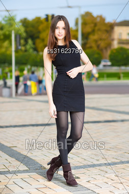 Attractive Young Woman In Black Dress Posing Outdoors Stock Photo