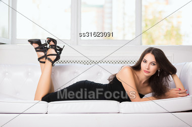 Attractive Young Woman In Black Fitting Dress Posing On The Sofa Stock Photo