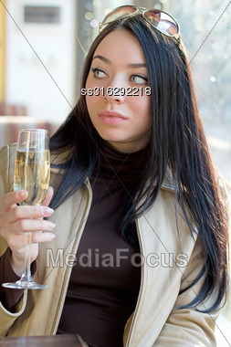 Attractive Young Woman With A Glass Of Champagne Looking Away. Isolated On White Stock Photo