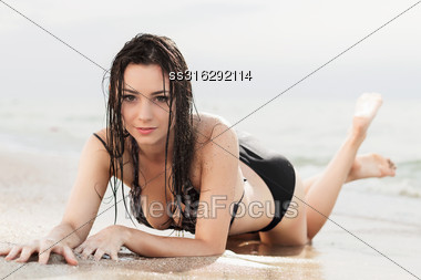 Attractive Young Woman Posing In Wet Swimsuit On The Beach Stock Photo