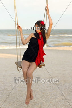 Attractive Young Woman Sitting On A Swing Stock Photo