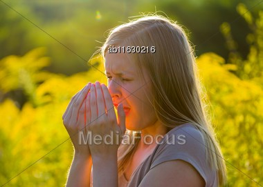 Attractive Young Woman Sneezing Because Of Asthmatic Allergy In Summer Nature Stock Photo