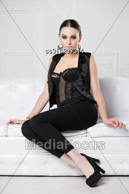 Attractive Young Woman Wearing Black Clothes Posing On The Sofa Stock Photo