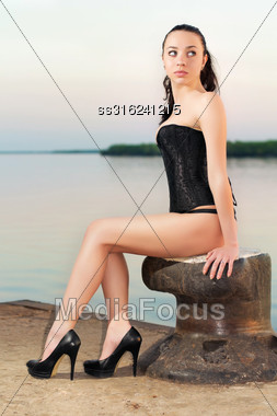 Attractive Young Woman Wearing Black Corset And High Heels Posing On The Pier Stock Photo