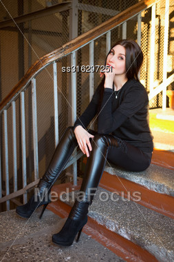 Attractive Young Woman Wearing Fashionable Clothes Posing On The Stair Stock Photo