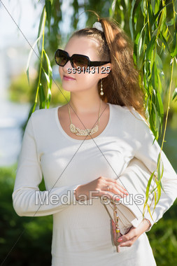 Attractive Young Woman Wearing White Dress And Black Sunglasses Posing Outside Stock Photo