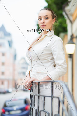 Attractive Young Woman Wearing White Jacket Posing Outdoors Stock Photo