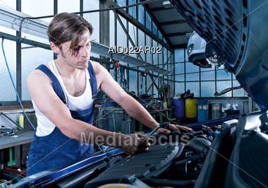 Auto Mechanic Working On Engine Stock Photo