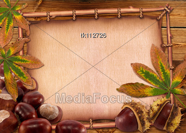 Autumn Chestnuts And Leaves On Old Paper Background Stock Photo