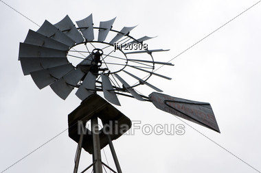 Back Lit Portrait Of An Old Fashioned Farm Windmill. Stock Photo