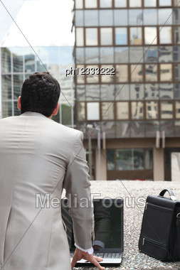 Back View Of A Businessman Standing Outside With Computer And Briefcase Stock Photo