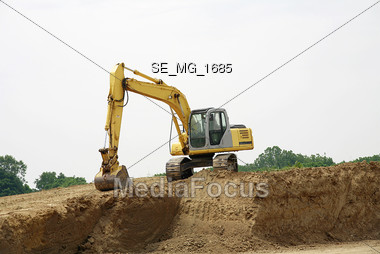 Backhoe on a Pile of Dirt Stock Photo
