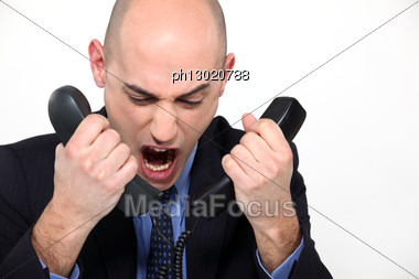 Bald Man Shouting Into Two Telephones Stock Photo