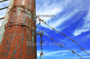 Barbed Wire On The Pole Against The Blue Sky Stock Photo
