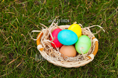 Basket With The Colorful Easter Eggs On The Grass Stock Photo