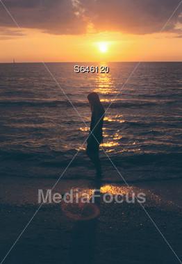 Beach Sunset with Girl Walking Stock Photo
