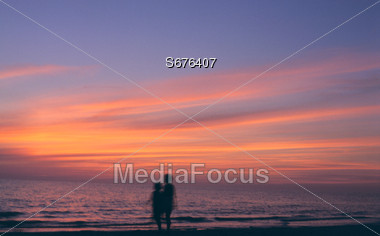 Beach Sunset with People Walking Stock Photo