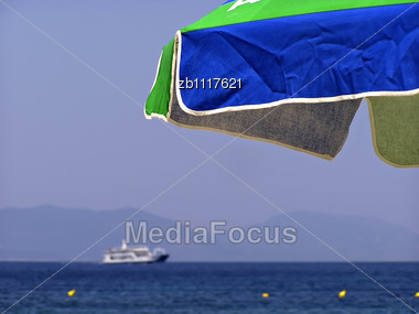 Beach Umbrella, Blured Ferry At Background, Clear Blue Sky Stock Photo