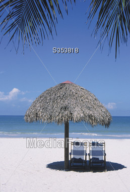 Beaches - Beach Chairs with Palm Leaf Umbrella Stock Photo