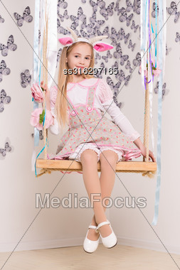Beautiful Blond Girl Wearing Goat Costume Posing On The Swing Stock Photo