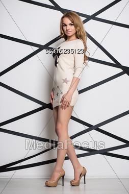 Beautiful Blond Woman Posing In Beige Short Dress Stock Photo