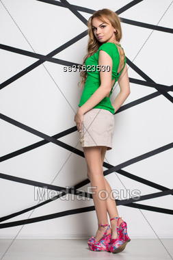 Beautiful Blond Woman Posing In Green T-shirt And Beige Skirt Stock Photo