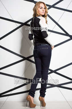 Beautiful Blond Woman Wearing Fashionable Clothes Posing Near The Wall Stock Photo