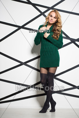 Beautiful Blond Woman Wearing Green Knitted Dress Posing In The Studio Stock Photo