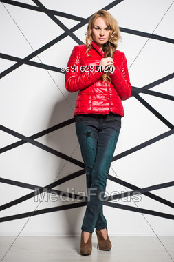 Beautiful Blond Woman Wearing Jeans And Red Jacket Posing In The Studio Stock Photo