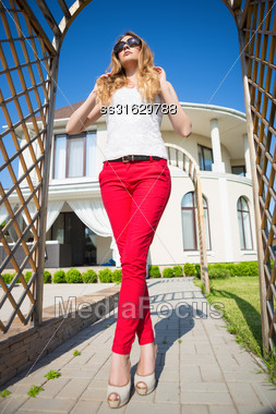 Beautiful Blond Woman Wearing White Top And Red Panties Posing In Archway Outdoors Stock Photo