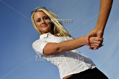 Beautiful Blonde Girl Shakes Hands With Another Girl. Handshake Stock Photo