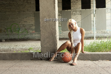 Beautiful Blonde Girl Is Sitting With Basketball On The Street Stock Photo
