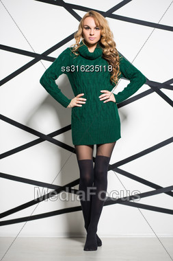 Beautiful Blonde Wearing Green Knitted Dress Posing In The Studio Stock Photo